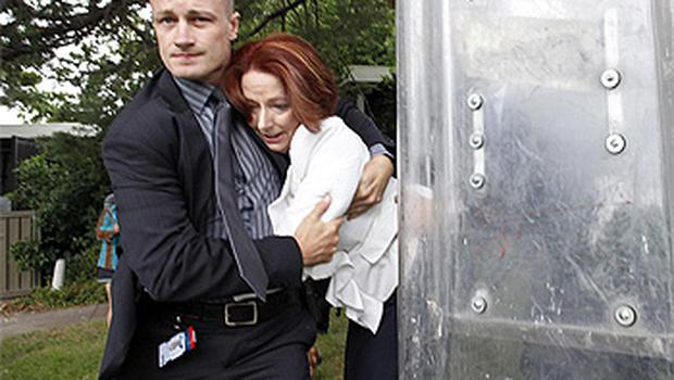 A body guard protects Australian Prime Minister Julia Gillard as she is taken to safety