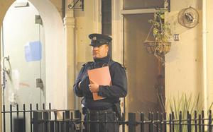 An officer stands outside the victim's flat