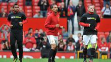 Manchester United's Rio Ferdinand (centre) during the warm up as his teammates Wayne Rooney (right) and Oliveira Anderson (left) wear Kick It Out anti-racism campaign t-shirts during the Barclays Premier League match at Old Trafford, Manchester. Photo: PA