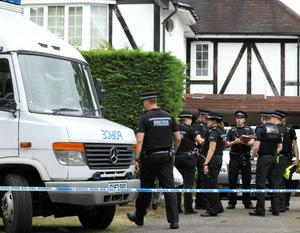Police Officers stand outside the home of Saad al-Hilli in Claygate, south of London September 10, 2012.  Police searching the home of a British family found shot dead in the French Alps last week evacuated neighbouring properties on Monday after saying they had discovered unspecified items that had caused them concern.    REUTERS/Olivia Harris (BRITAIN - Tags: CRIME LAW SOCIETY TPX IMAGES OF THE DAY)