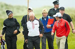 Caroline Wozniacki and Rory McIlroy share a joke with Rory's father, Gerry, on the ninth fairway