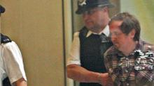 A man is handcuffed and removed after attacking Rupert Murdoch at the Commons hearing