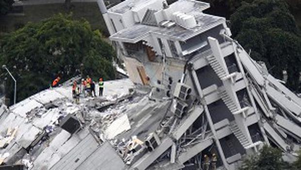 Rescue workers climb onto the collapsed Pyne Gould Guinness Building in central Christchurch, New Zealand (AP)