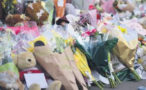 Floral tributes outside the scene of the horrific house fire in Derby, England yesterday.