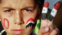 A Syrian boy with the national flag painted on his fingers, takes part in a protest against Syria's President Bashar al-Assad. Photo: Reuters