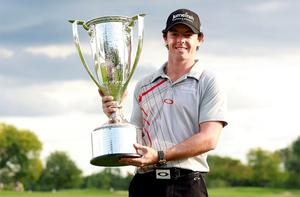 Rory McIlroy poses with the champion's trophy after winning the PGA Championship golf tournament in Carmel, Indiana