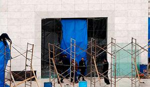 A Palestinan worker takes down a tarp that was put up in fronmt of the grave of the late Palestinian leader Yasser Arafat after his body was exhumed.