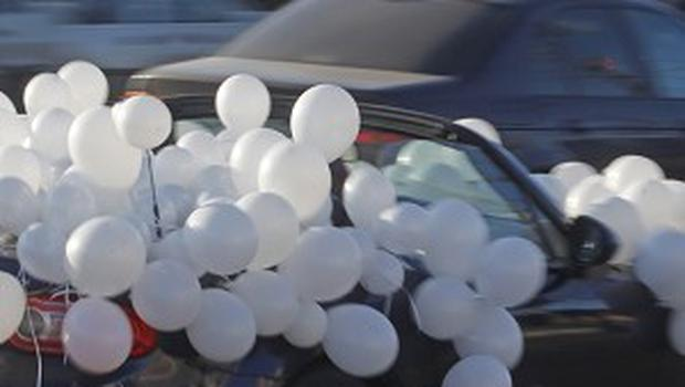 In a bid to show support for a movement against Vladimir Putin, thousands of cars have flown white ribbons and balloons (AP)