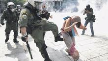 A Greek riot police officer kicks a protester who was trying to calm others down in clashes in Athens' Syntagma Square yesterday