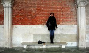 A woman stands on a bench above a flooded street in Venice.