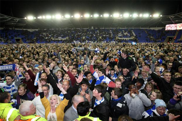 Reading fans invade the pitch after their team secured promotion to the Premier League at the Madejski Stadium. Photo: PA