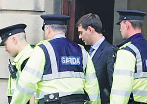Sean Quinn Jnr is escorted by gardai as he leaves the High Court yesterday bound for Mountjoy jail after being found in contempt of court. Photo: Courtpix