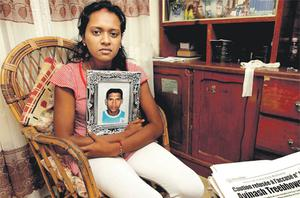 Reshma Treebhowon, wife of Avinash Treebhowon, holds a photograph of her husband at her parents' home in Northern Mauritius last night