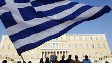 Protesters raised a Greek flag in front of parliament during a rally against austerity measures in Athens yesterday. Photo: Reuters