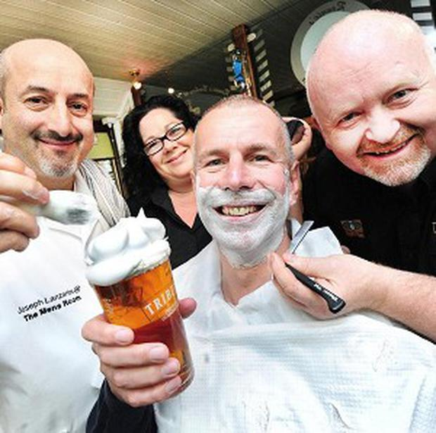 Barber Joseph Lanzante, left, Roger Ryman, of St Austell Brewery, and landlord Malcolm Putko, right, at the Western Inn (Wild Card PR/PA)