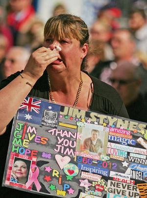 A woman weeps as she watches the television broadcast outside of the State Funeral held for former AFL player Jim Stynes at St Paul's Cathedral. Photo: Getty Images