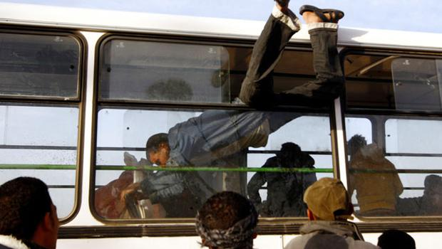 PANIC: A refugee clambers into a bus at a camp after crossing into Tunisia to flee the violence in Libya. Photo Yannis Behrakis/Reuters