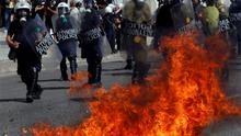 A molotov cocktail explodes beside riot police officers near Syntagma square during a 24-hour labour strike in Athens. Photo: Reuters