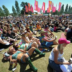 People sit on the ground at the Isle of Wight Festival after folding chairs were banned
