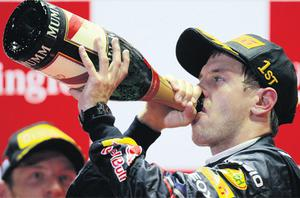 Sebastian Vettel takes a celebratory swig from a bottle of champagne after his emphatic success in yesterday's Singapore Grand Prix