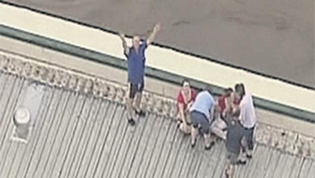 People are seen on the rooftop of a house in Grantham, a township between Toowoomba and Brisbane, in this still image taken from video