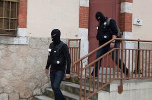 Masked officers exit the building following the  operation that killed Mohammed Merah