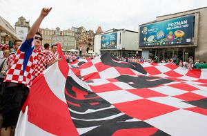 A Croatian supporter holds a large flag as he cheers