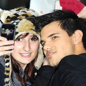 Taylor Lautner has his photo taken with a fan as he arrives at the premiere of new film Abduction