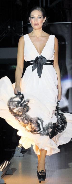 Sheila Eustace enjoys her time again on the catwalk, wearing a white dress with black detail from Beverly Hills