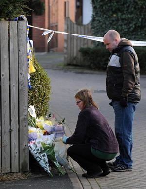 Members of the public lay flowers at the police cordon Photo: PA