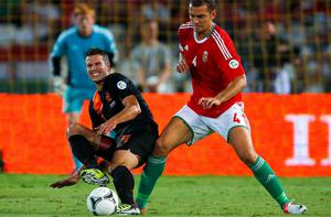 Holland's Robin van Persie is tackled by Hungary's Roland Juhasz
