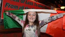 Emily Bates, 9, cheers on Mary with a best of luck sign in the background