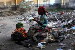 A boy eats as he sit on his merchandise at the ruins of Petion Ville market in Port-au-Prince, Haiti, yesterday. But while food and supplies have reached the capital, survivors in towns nearby are desperately waiting for help to arrive