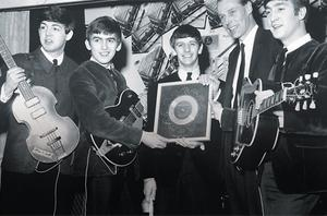 The magic touch: The Beatles, with George Martin, holding their silver disc for 'Please, Please Me' in 1963