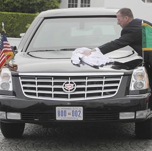 A secret service agent cleans rain water off the presidential car