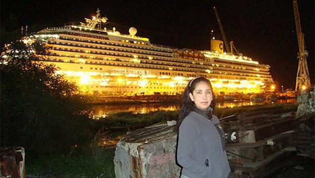 Crew member Erika Soria poses in front of the Costa Concordia cruise ship