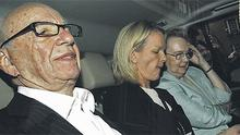 Rupert Murdoch (left) is driven from his apartment in London yesterday flanked by his daughter Elisabeth, centre, and another companion