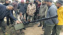 A rebel army officer teaching civilian volunteers how to fire an anti-aircraft gun