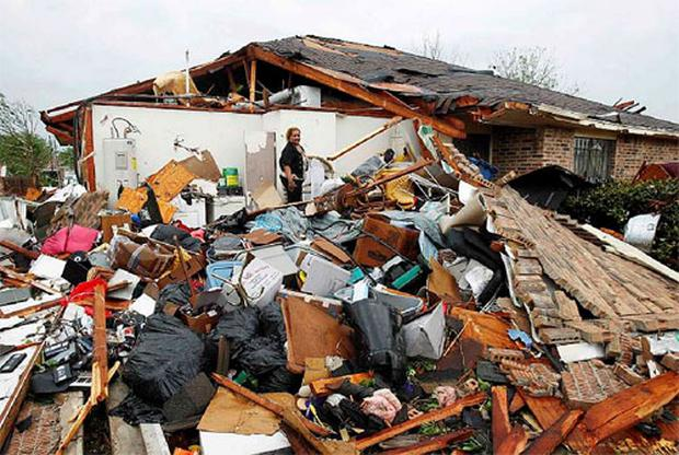 A resident sorts through the remains of her damaged home after a series of tornadoes ripped through the Dallas suburb of Lancaster, Texas.