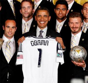 U.S. President Barack Obama holds a team jersey as he poses with members of the 2011 Major League Soccer champions, Los Angeles Galaxy soccer team, in the East Room at the White House in Washington.
