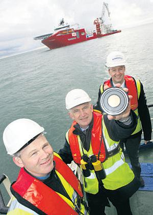 EirGrid chief executive Dermot Byrne – with John Fitzgerald and Paul O'Rourke – holds up a piece of the cable