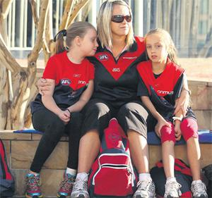 Meagan Battye watches with daughters Brylee and Lainie outside the church in Melbourne early today