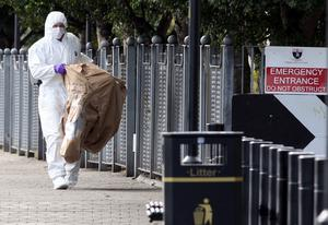 A forensic officer at the scene outside the main council offices, beside the River Foyle, in Derry, after dissident republicans attached a bomb to a bicycle as part of a trap to kill police. Photo: PA