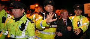 Gardai escort Taoiseach Enda Kenny past protesters in Co Galway