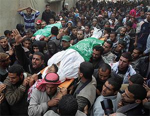 Palestinians carry the bodies of Hamas militants, who were killed in Israeli air strikes in the central Gaza Strip