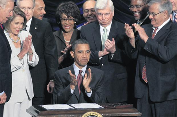 US President Barack Obama joins the applause of lawmakers after signing the Dodd-Frank Wall Street Reform and Consumer Protection Act in Washington yesterday. It is the most comprehensive financial regulatory overhaul of banks since the Great Depression