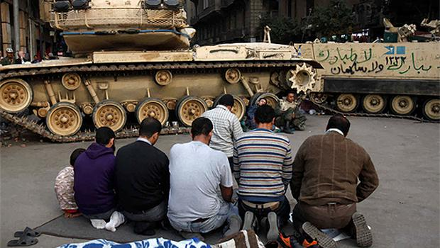 Egyptian protesters pray near army tanks in Tahrir square in Cairo yesterday on the sixteenth day of the protest. Photo: Reuters