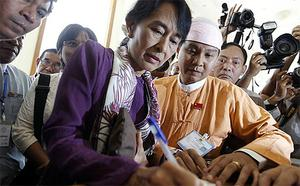 Burmese pro-democracy leader Aung San Suu Kyi signs the register as she arrives at the lower house of parliament in Naypyitaw
