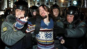 Policemen detain an activist during a rally to protest against the results of the parliamentary elections in Russia
