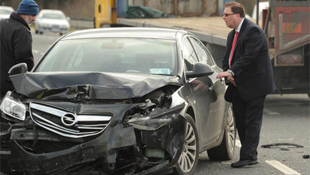 Kerry North Fianna Fail TD Tom McEllistrim inspects the damage to his car
